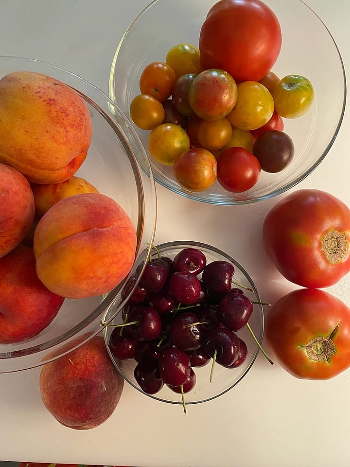 Cherries in a bowl, peaches in a bowl and tomatoes